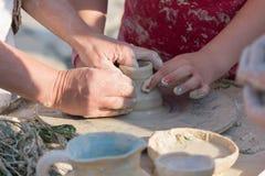 Händer av ett barn som lär krukmakeri arkivbilder