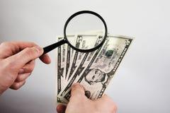 Händer av ett hållande förstoringsglas för ung man och dollarräkningar Royaltyfria Bilder