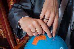 Händer av ett ungt par på fingerjordklotet Royaltyfri Fotografi