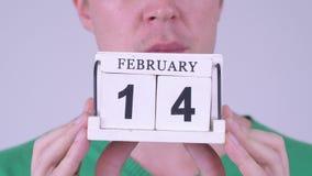 Händer av för innehavkalender för ung man som kvarteret är klart för valentin dag lager videofilmer