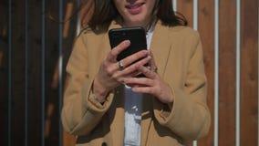 Händer av för innehavsmartphone för ung kvinna det fria i soligt väder stock video