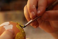 Händer av fem år gammal hjärta för flickamålningguling på det blowed easter ägget med den tunna borsten royaltyfri fotografi