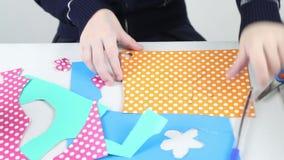 Händer av flickaattraktioner blommar på kulört papper och snitt för hantverk arkivfilmer