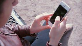Händer av flickan med telefonen stock video