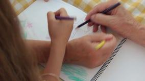 Händer av flickan och morföräldrar som tillsammans drar lager videofilmer