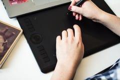Händer av flickan på en grafisk minnestavla Arkivfoton