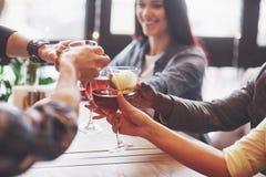 Händer av folk med exponeringsglas av whisky eller vin som firar och rostar i hedern av bröllopet eller annan beröm royaltyfria bilder