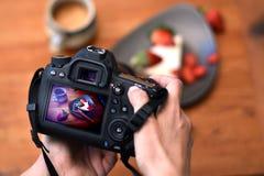 Händer av fotografen som rymmer dslrkameran som tar ett foto av en jordgubbeefterrätt royaltyfri fotografi