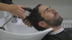 Händer av frisören häller vatten till ett hår för klient` s Klienten tvättar hår, når han har klippt i frisersalong close upp 4K Arkivbild
