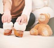 Händer av gravida par med små kängor för behandla som ett barn Arkivbild