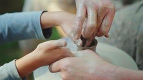Händer av keramikern undervisar barnet hur man gör krukor Begrepp - överföring av erfarenhet som utbildar royaltyfri foto