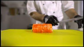 Händer av kocken som förbereder japansk mat, kock gör sushi, förbereder sushirulle, klippte dem till stycken stock video
