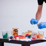 Händer av konstnären, palettborstar, olika färger Konstnärhjälpmedel för riktig konst och inspiration m?rk lampa ovanf?r sikt Oss royaltyfria foton