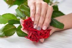 Händer av kvinnan med rosor Arkivfoton