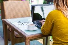 Händer av kvinnan på tangentbordet av hennes bärbar datordator Kvinnligt arbete på bärbara datorn i ett gatakafé, Arkivbild