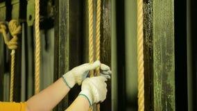 Händer av kvinnan platsen av arbete i handskar lyfter teatergardinen med en kabel och fäster den lager videofilmer