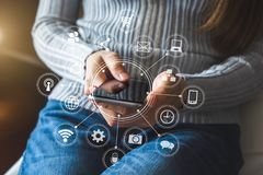 Händer av kvinnan som använder mobiltelefonen i modernt kontor med bärbara datorn och den digitala minnestavladatoren arkivfoto