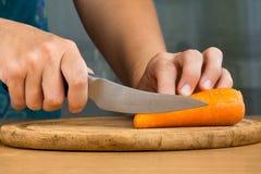 Händer av kvinnan som klipper en morot Arkivfoton