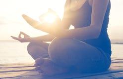 Händer av kvinnan som mediterar på en yoga, poserar på stranden Arkivfoton