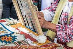 Händer av kvinnan som väver traditionellt på en liten vävstol Royaltyfria Foton
