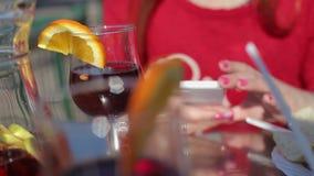 Händer av kvinnlign med smartphonen och exponeringsglas av rött vin arkivfilmer