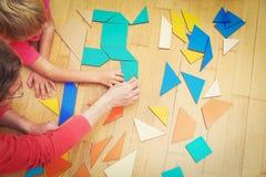 Händer av läraren och barnet som spelar med geometriska former Royaltyfri Bild