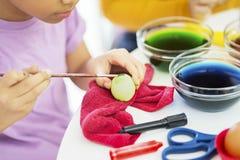 Händer av lilla flickan som hemma färgar ägg för påsk royaltyfri fotografi