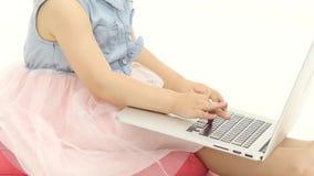 Händer av lite flickaapplåden på tangenterna av bärbara datorn Vit bakgrund stock video