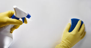 Händer av lokalvårdpersonalen med skurnylon- och sprejarearbete Arkivfoton