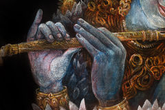 Händer av lordkrishnaen som spelar flöjten, detalj med lotusblommamodellen Arkivbild