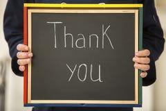 Händer av män som rymmer en kritisera, stiger ombord med skriftliga ord: Tacka dig royaltyfria bilder