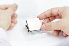 Händer av manligt tar ut CPUen ut ur asken Royaltyfri Foto