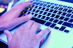 Händer av mannen fungerar bak en bärbar dator Fotografering för Bildbyråer