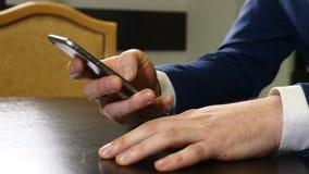 Händer av mannen i dräkten som rymmer den svarta smartphonen Manliga fingrar som knackar lätt på mobiltelefonskärmen Contactless  arkivfilmer