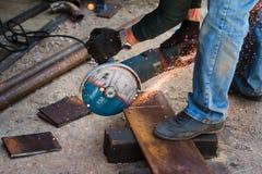 Händer av mannen med stålskärarehjälpmedlet Arbetaren utanför, klipper arket av metall Elektriskt s?g utveckling av varma gnistor royaltyfria bilder