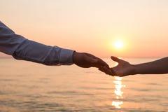 Händer av mannen och kvinnan som till varandra når fotografering för bildbyråer