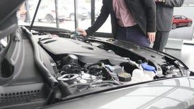 Händer av mannen som använder blått mikrofibertyg för att göra ren bilmotorn arkivfilmer