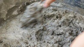 Händer av mannen som använder murslevblandningmortel för diy fast cement, hårdnar lager videofilmer