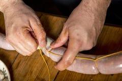 Händer av mannen som gör salame arkivbild