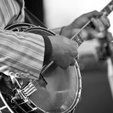 Händer av mannen som spelar banjon arkivbild