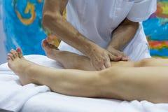 Händer av massören och klientens fot under en massagebehandling Royaltyfria Bilder