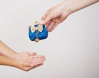 Händer av modern ger handväskan till lite flickan Royaltyfria Foton