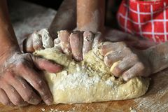Händer av modern och dottern som tillsammans knådar deg i köket royaltyfria bilder