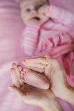 Händer av modern som rymmer ömt en mycket liten babys ben Royaltyfri Bild
