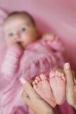 Händer av modern som rymmer ömt en mycket liten babys ben Arkivbilder