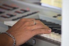 Händer av musikern att spela tangenterna av den elektroniska synthen royaltyfri fotografi