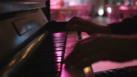 Händer av musikern som spelar tangentbordet i konsert i nattklubb lager videofilmer