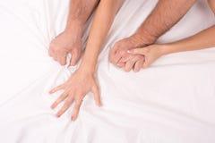 Händer av par som danandeförälskelse i säng på det vit skrynkliga arket, fokus på händer arkivbild