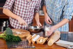 Händer av parstrykägg och matlagning tillsammans på kök Royaltyfria Foton
