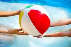 Händer av pysen och flickan som spelar med den mång- kulöra strandbollen i simbassäng fotografering för bildbyråer